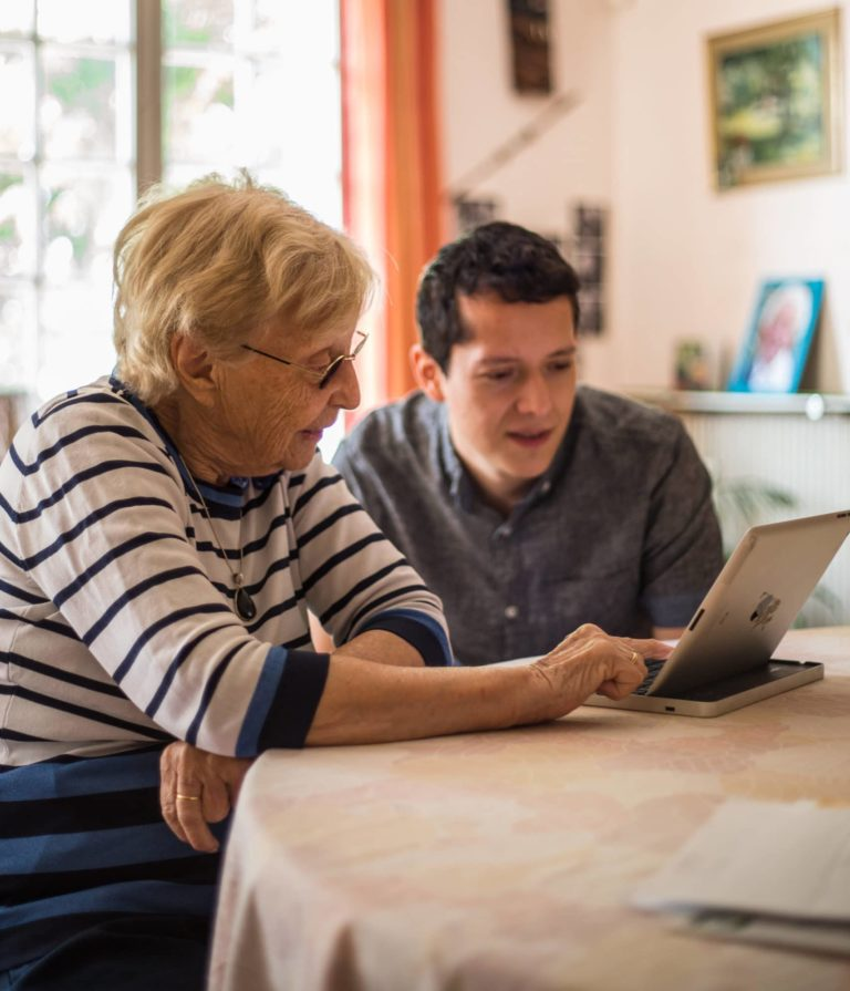 une sénior et un jeune devant un ordinateur