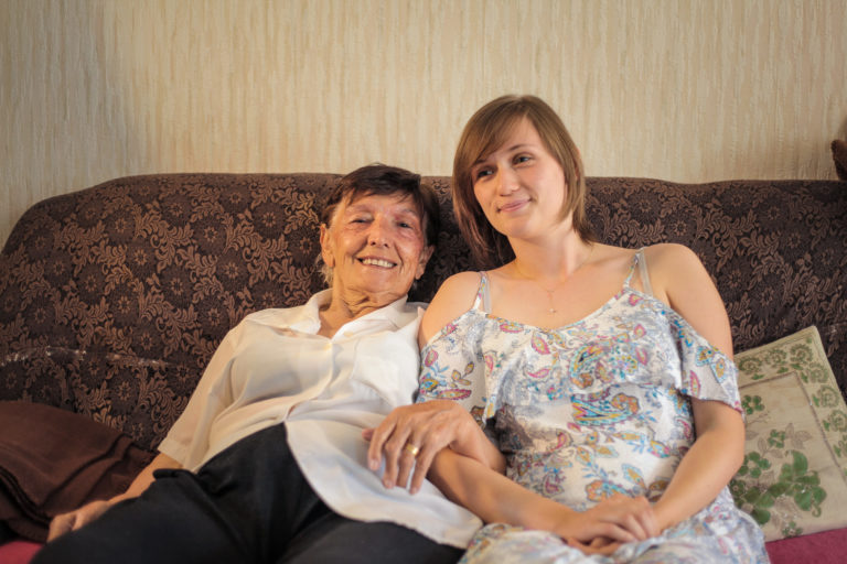 Partage 1 Toit : une sénior et une jeune sur un canapé